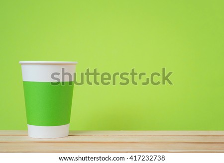 Paper cup with Sleeve on green background - stock photo