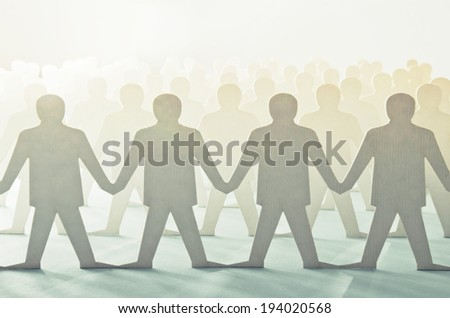 Paper cut figures standing in rows - stock photo