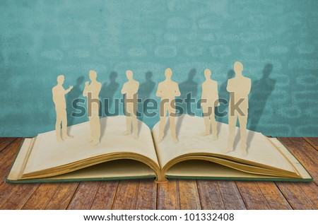 Paper cut of  business man  on old book - stock photo