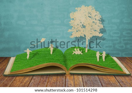 Paper cut of children play on old grass book - stock photo