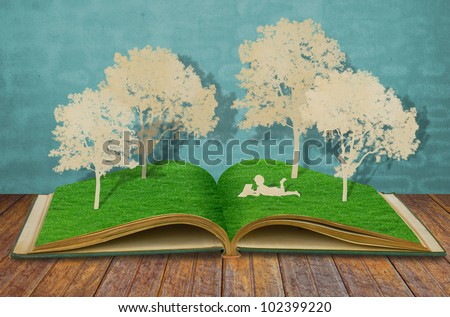 Paper cut of children read a book under tree on old book - stock photo