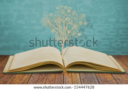 Paper cut of christmas tree with snowflakes on old book