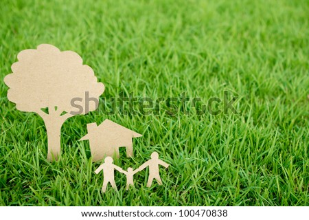 Paper cut of family with house and tree on fresh spring green grass - stock photo