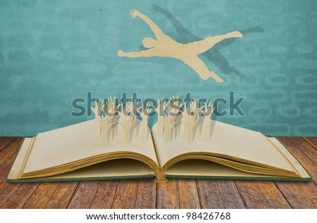 Paper cut of man jump over jubilant crowd on book - stock photo