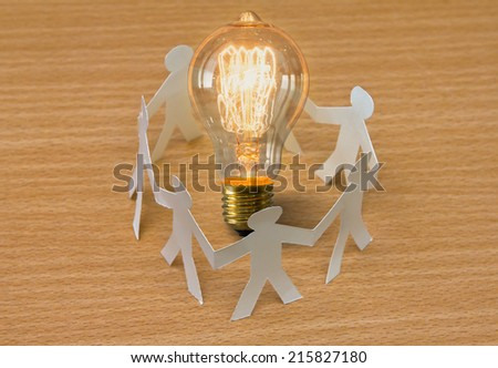 Paper cut of people standing in a circle around bulb of idea - stock photo