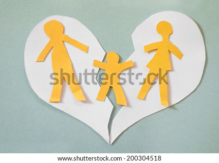 Paper cutout family split apart on a paper heart - divorce concept                                - stock photo