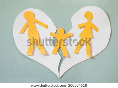 Paper cutout family split apart on a paper heart - divorce concept                                - stock photo
