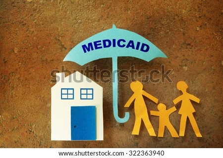 Paper cutout family with house under a Medicaid umbrella                                - stock photo