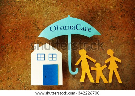 Paper cutout family with house under an Obama Care umbrella                                - stock photo