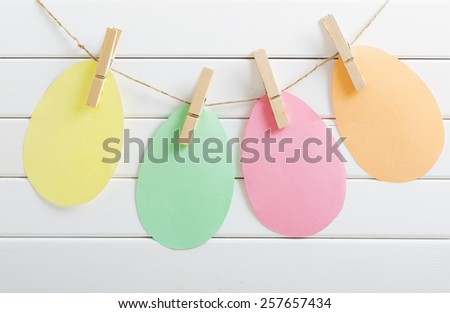 paper Easter eggs on white wooden background - stock photo