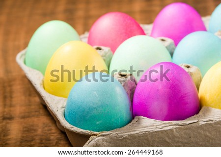 Paper egg carton of colorful naturally dyed Easter eggs - stock photo