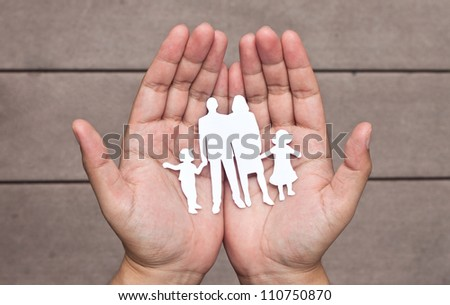 Paper family in hands on brown wood background - stock photo