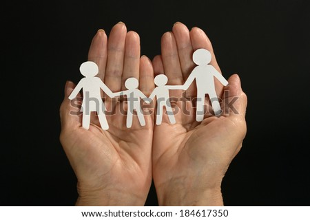 Paper  family in hands  on dark background