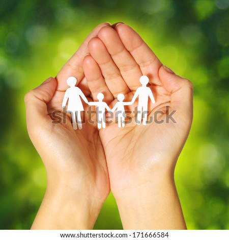 Paper Family in Hands over Green Sunny Background. Family and Kids Concept - stock photo