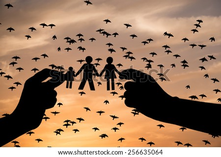 Paper Family in Hands with Silhouettes of flying birds - stock photo