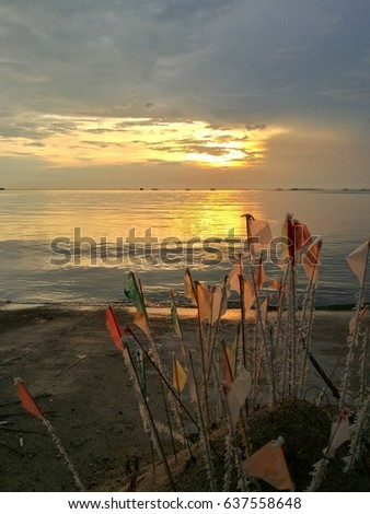paper flag and golden sunset at the quiet beach