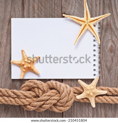 Paper for copy space and rope on wooden textured background