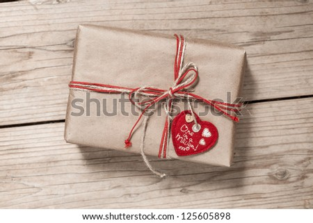 paper gift box with red bow and heart on wooden background - stock photo