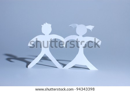 Paper girl and boy holding on hands and forming heart between figures - stock photo