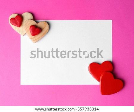 Paper greeting card and decorative hearts on pink background