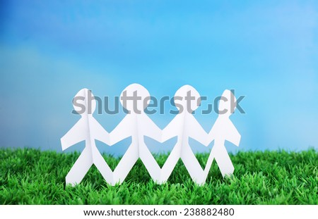 Paper group of people holding hands on green grass on blue background - stock photo