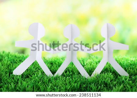 Paper group of people holding hands on green grass on light background - stock photo