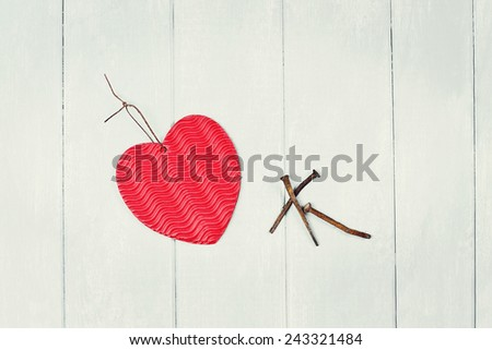 Paper heart and three rusty nails with room for copy space. - stock photo