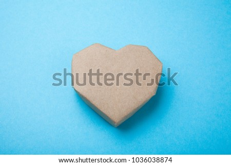 Paper heart made from recycled paper on a blue background.