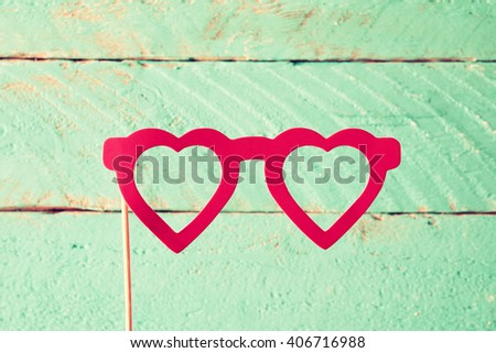 paper heart shape fake glasses in sticks in front of wooden background. vintage filtered image