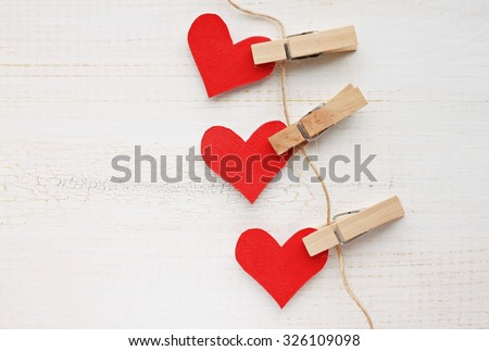Paper heart wall garland - DIY valentines decor idea, pinned on twine, white wooden background - stock photo