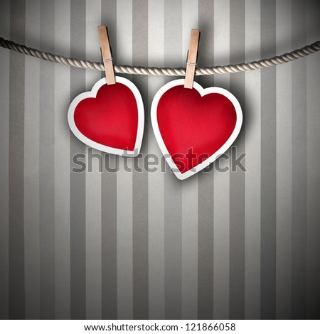 Paper hearts hanging on a rope on grunge background