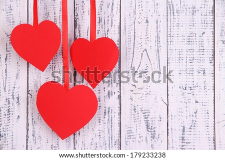 Paper hearts on wooden background - stock photo