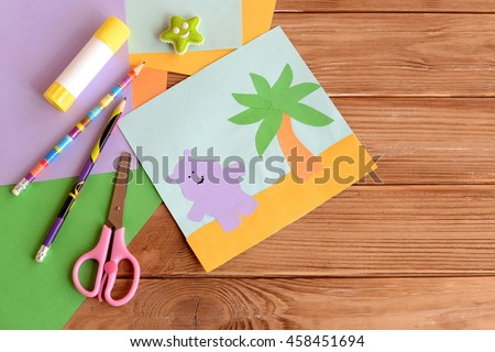Paper hippo and palm tree applique, colored paper sheets, scissors, pencils, glue, eraser on wooden background with blank space for text. Funny children background. Art and craft project for kids  - stock photo