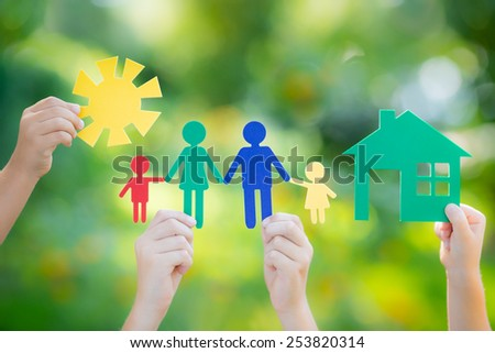 Paper house and family in hands against spring green background. Real estate business concept - stock photo