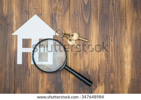 paper house and key with Magnifying Glass, House hunting on wooden background - stock photo