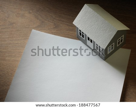 paper house and sheet of paper on the table
