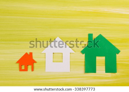 Paper house figure on green wooden background. Comparing houses. Eco house Green housing. Real Estate Concept. Top view.