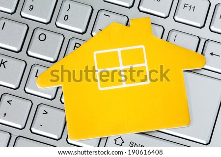 Paper house icon on the computer keyboard. Web hosting or real estate on the internet concept. - stock photo