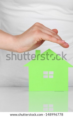 Paper house in hand isolated on white