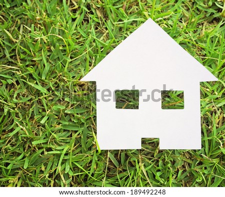 Paper house on green grass