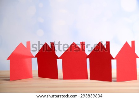 Paper houses on bright background - stock photo