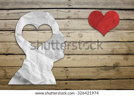 Paper humans head with heart on wood deck background - stock photo