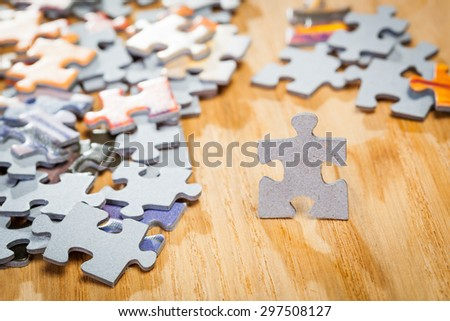Paper jigsaw puzzle by pieces  on a table. Shallow depth of field