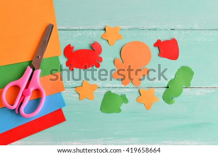 Paper kids crafts. Cut from paper figures. Set of sea inhabitants. Sheets of colored paper, scissors. Set for kids art.  - stock photo