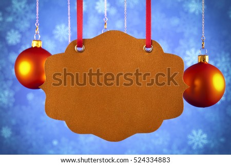 Paper label and christmas baubles on blue background