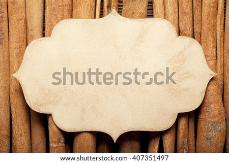 Paper label and cinnamon sticks on wooden wall background