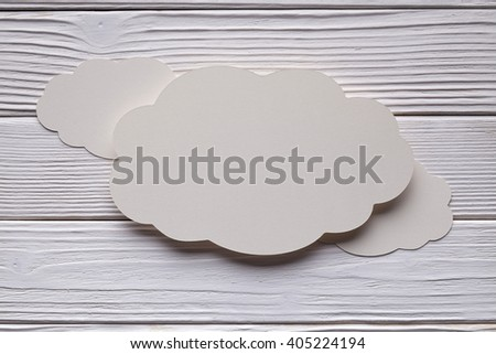Paper label in shape of cloud on wooden background  - stock photo