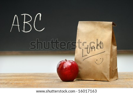 Paper lunch bag on desk with apple - stock photo