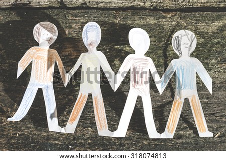Paper made people figures. Painted white figures on wooden board