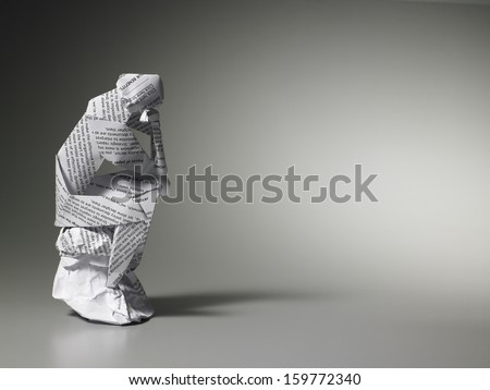Paper man deep in thought sitting on rock - stock photo